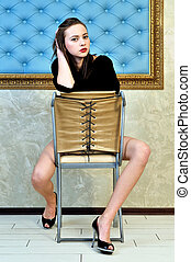 beautiful woman sitting on the chair in a beautiful interior.