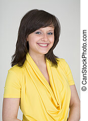 Portrait of the beautiful young girl in yellow dress