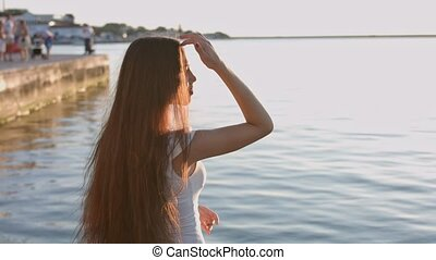 Portrait of the beautiful young woman in the white dress by the sea