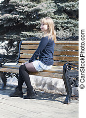 Portrait of the beautiful young woman on a bench in the park.
