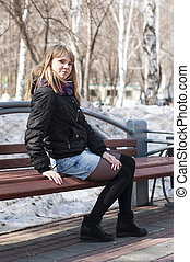Portrait of the beautiful young woman sitting on a bench in the park.