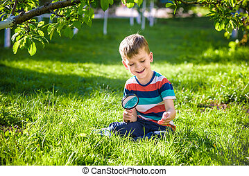 portrait of the boy in a garden, considers plants through a magnifying glass.