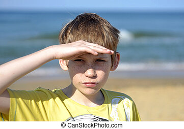 Portrait of the boy of the teenager looking afar on the seashore.