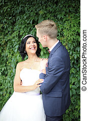 bride and groom on a background of green leaves