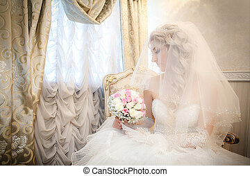 Portrait of the bride with a wedding bouquet from roses in the hand sitting on a sofa near a window