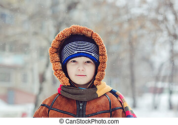 Portrait of the charming baby, surrounded by snow