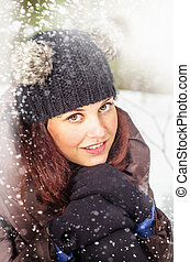 Portrait of the charming young woman in winter outdoors