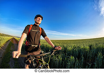 Portrait of the cyclist with mountain bike on a background of blue sky with clouds.
