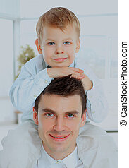 portrait of the father holding his son on his shoulders. both look at the camera and smiling.