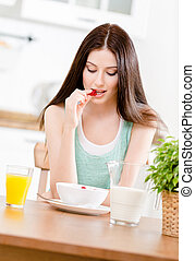 Portrait of the girl eating dieting muesli with milk and...