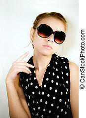Portrait of the girl in sunglasses on a light background
