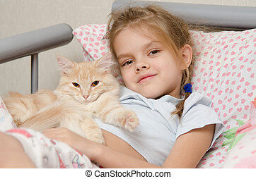 Portrait of the girl with a cat lying in bed