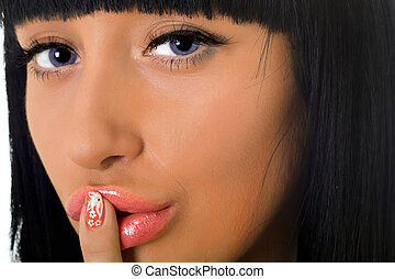Portrait of the girl with a finger at lips