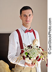 portrait of the groom with a bouquet in hands