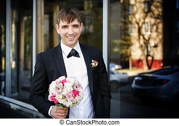 Portrait of the groom with a wedding bridal bouquet