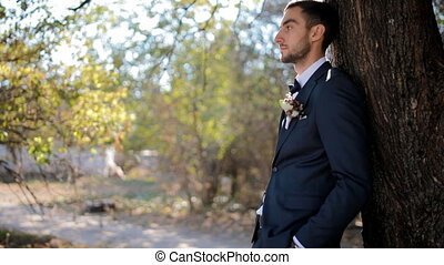 Portrait of the groom.Young man near the tree.