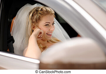portrait of the happy bride in a car