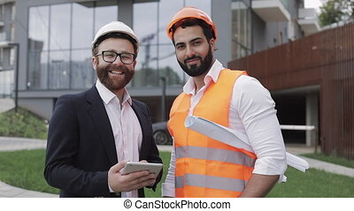 Portrait of the happy builder and businessman looking at the camera standing against the backdrop of a modern building. Professions, construction, workers, architect concept.