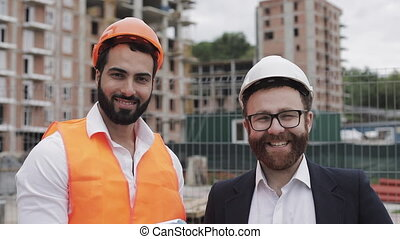 Portrait of the happy builder and businessman looking at the camera standing on the construction site background. Professions, construction, workers, architect concept.