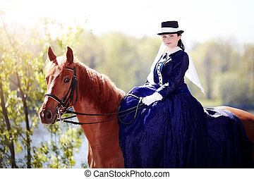 Lady on a horse. The lady on riding walk. Portrait of the horsewoman. The woman astride a horse. The aristocrat on riding walk.
