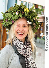Portrait of the laughing girl in an oak wreath