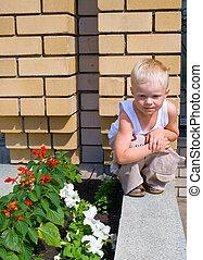 little boy against yellow brick wall