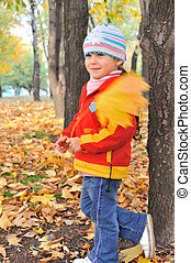 Portrait of the little girl in autumn forest. Seasonal photo