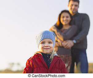 Portrait of the little girl with a funny hat outdoors and man and woman holding hands