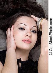 Portrait of the loveky lady lying on grey fur coat