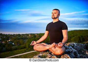 Portrait of the man sitting on a rock in the lotus position against blue sky.