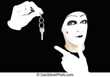 Portrait of the mime in white gloves with a key