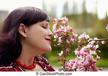 Portrait of the nice young woman with a blossoming branch