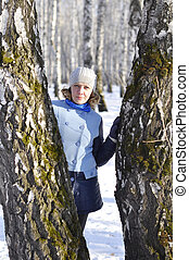 Portrait of the Russian woman in the birch wood in the winter.