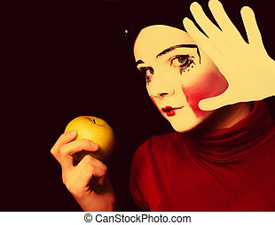 sad mime with an apple on a black background