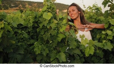 Portrait of the smiling girl between the vineyard leaves