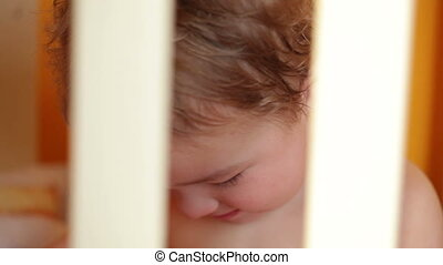Portrait of the smiling little boy in the playpen.