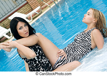 Portrait of the two sexy girlfriends in pool