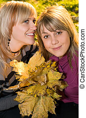 Portrait of the two young beauty blonde with autumn leaves