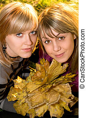 Portrait of the two young blonde with autumn leaves