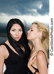 Portrait of the two young women against the cloudy sky