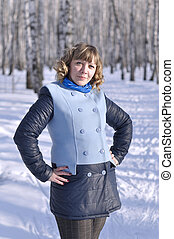 Portrait of the woman of average years in the birch wood in the winter.
