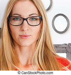 Portrait of the woman wearing black eye glasses looking at...
