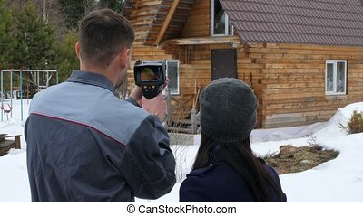Portrait of the worker of the house which is carrying out an inspection by the thermal imager. To show to the customer problem places. Energy saving.