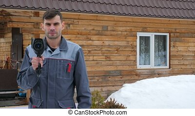 Portrait of the worker of the house which is carrying out an inspection by the thermal imager. To look for losses of heat. Fight against heatlosses. Energy saving.