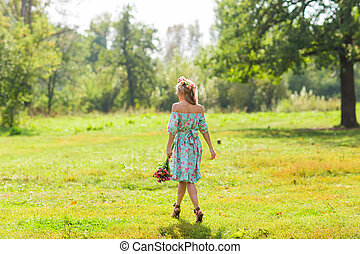 Portrait of the young beautiful romantic woman in dress outdoors