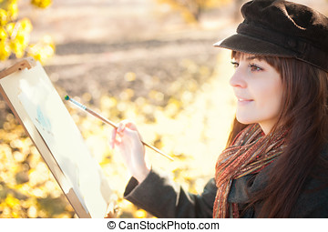 Portrait of the young beautiful woman with a brush in her hand