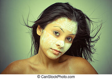 Portrait of the young brunette , Cosmetician make mask to girl. Facial massage.