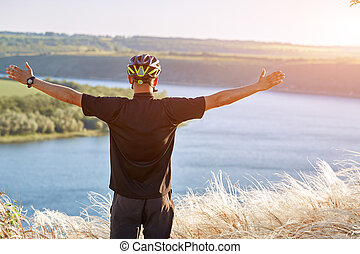 Portrait of the young cyclist standing on the hill above the river against blue sky with clouds.