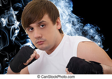 Portrait of the young fighter in a smoke