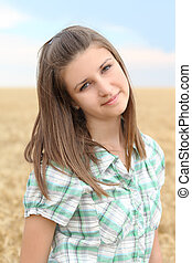 Portrait of the young girl in the wheat field